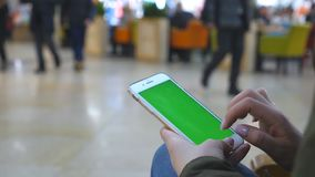 Female hands using modern smartphone with green screen. Young girl sitting at bench in shopping mall and tapping at. Touch screen of cell phone with chroma key stock footage