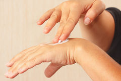 Female hands using a moisturizer for the skin Stock Image
