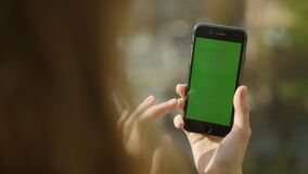 Female hands using phone with green screen. Girl hands holding phone outdoorss.