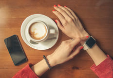 Female hands using smart watch with blank screen with coffee Stock Image