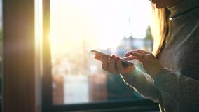 Female hands using smartphone against a blurred cityscape in the setting sun stock video