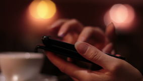 Female hands using a smartphone in cafe. Muffled light close-up full hd stock video