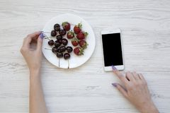 Female hands using smartphone while eating cherries and strawberries on white wooden background, top view. stock photos