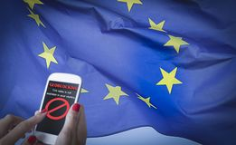 Female hands using a smartphone with Geo-blocking on screen. and EU flag on the background. Female hands using a smartphone with geoblocking on screen and EU royalty free stock photos