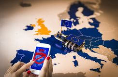 Female hands using a smartphone with Geo-blocking on screen. and Padlock over EU map. Female hands using a smartphone with geoblocking on screen and Padlock over stock images