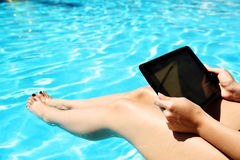 Female hands using tablet computer. Closeup portrait of a female hands using tablet computer in swimming pool Royalty Free Stock Photography
