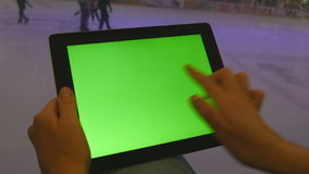 Female hands using tablet pc with green screen in shopping mall. Lot of people skate on indoor ice rink at the. Background stock video