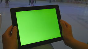 Female hands using tablet pc with green screen in shopping mall. Lot of people skate on indoor ice rink at the. Background stock footage