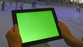 Female hands using tablet pc with green screen in shopping mall. Lot of people skate on indoor ice rink at the. Background stock video footage