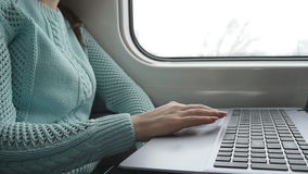 Female hands using touchpad of laptop pc in train. Arm of young woman touching touchscreen of notebook during traveling stock footage