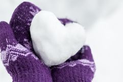 Female hands in warm knitted mittens keep the heart from snow. Against the background of white snow, with soft focus stock image