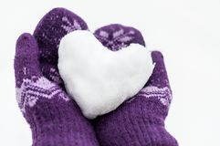 Female hands in warm knitted mittens keep the heart from snow. Against the background of white snow stock image