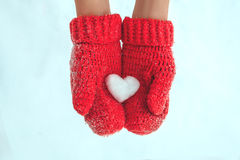 Female hands in warm red crocheted mittens with snowy heart. Whi Royalty Free Stock Photo