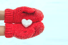 Female hands in warm red crocheted mittens with snowy heart. Whi royalty free stock images