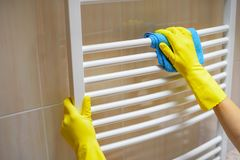 Female hands wash the radiator. royalty free stock photos