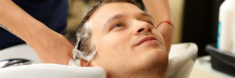 Female hands washing hair to handsome smiling man. At hairdresser with shampoo before haircut. Keratin restoration, latest trend, fresh idea, haircut picking Royalty Free Stock Images