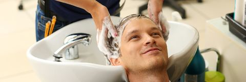 Female hands washing hair to handsome smiling man. At hairdresser with shampoo before haircut. Keratin restoration, latest trend, fresh idea, haircut picking Stock Photography