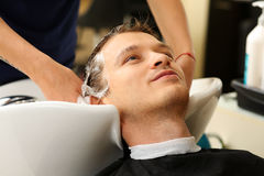 Female hands washing hair to handsome smiling man. At hairdresser with shampoo before haircut. Keratin restoration, latest trend, fresh idea, haircut picking Stock Photos
