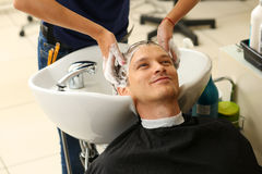 Female hands washing hair to handsome smiling man. At hairdresser with shampoo before haircut. Keratin restoration, latest trend, fresh idea, haircut picking Royalty Free Stock Photography