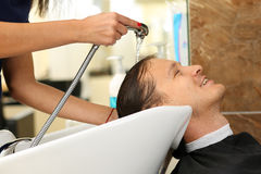 Female hands washing hair to handsome smiling man Stock Photography