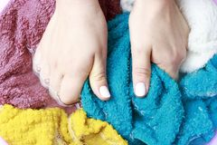 Female hands washing multicolored clothes in basin, top view stock photo