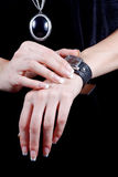 Female hands with a watch. Female beautiful hands with manicure touch a watch for time definition Stock Images