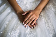 Female hands on the wedding dress stock photo