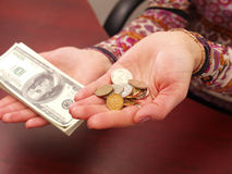Female hands weigh coins and denominations. Royalty Free Stock Photo