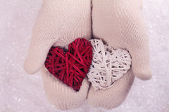 Female hands in white knitted cozy mittens holding two hearts   on a white snow background. Christmas tree decoration. Love concep Stock Photo