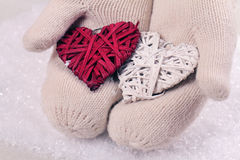Female hands in white knitted cozy mittens holding two hearts   on a white snow background. Christmas tree decoration. Love concep Royalty Free Stock Photography