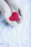 Female hands in white knitted mittens with entwined vintage romantic red heart on snow background. Love and St. Valentine concept Royalty Free Stock Photography
