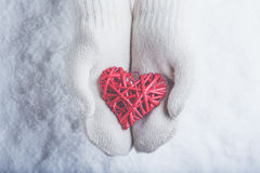 Female hands in white knitted mittens with entwined vintage romantic red heart on snow background. Love and St. Valentine concept Stock Image