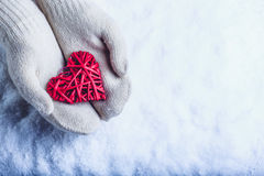 Female hands in white knitted mittens with entwined vintage romantic red heart on snow background. Love and St. Valentine concept Royalty Free Stock Photo