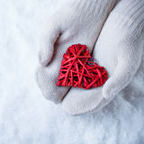 Female hands in white knitted mittens with entwined vintage romantic red heart on snow background. Love and St. Valentine concept Stock Photo