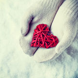 Female hands in white knitted mittens with a entwined vintage romantic red heart on a snow. Love and St. Valentine concept. Royalty Free Stock Photo