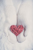 Female hands in white knitted mittens with a entwined vintage romantic red heart on a snow. Love and St. Valentine concept. Royalty Free Stock Image