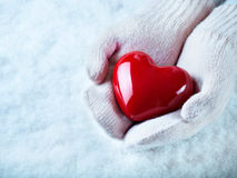 Female hands in white knitted mittens with a glossy red heart on a snow background.  Love and St. Valentine concept Royalty Free Stock Images