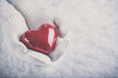 Female hands in white knitted mittens with a glossy red heart on a snow background.  Love and St. Valentine concept Stock Photography