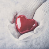 Female hands in white knitted mittens with a glossy red heart on a snow background.  Love and St. Valentine concept Royalty Free Stock Image