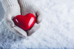 Female hands in white knitted mittens with a glossy red heart on a snow background. Love and St. Valentine concept. Royalty Free Stock Photo