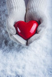 Female hands in white knitted mittens with a glossy red heart on a snow background. Love and St. Valentine concept. Stock Photography