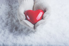 Female hands in white knitted mittens with a glossy red heart on a snow background. Love and St. Valentine concept. Stock Image