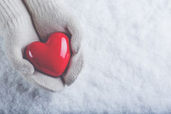 Female hands in white knitted mittens with a glossy red heart on a snow background. Love and St. Valentine concept. Stock Images
