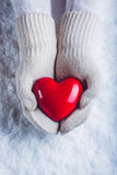 Female hands in white knitted mittens with a glossy red heart on a snow background. Love and St. Valentine concept. Royalty Free Stock Photos