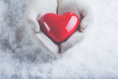 Female hands in white knitted mittens with a glossy red heart on a snow background. Love and St. Valentine concept. Royalty Free Stock Photography