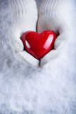 Female hands in white knitted mittens with a glossy red heart on a snow winter background. Love and St. Valentine cozy concept.  Stock Images