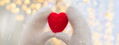 Female hands in white knitted mittens with red heart on glittering holiday background. St. Valentine Day concept banner royalty free stock photo