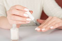 female hands with white nail varnish bottles stock image