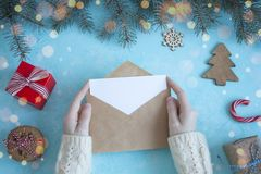 Female hands in a white sweater keep the Christmas letter in an envelope on a blue background.  royalty free stock images