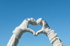 Female hands in the winter knitted gloves in the shape of a heart on the clear blue sky background. Concept royalty free stock images